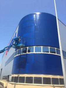 aplicando pintura antioxidante en fachada de nave industrial